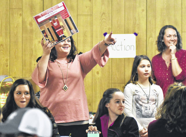 Julie Fuerst, left, to right, of Minster, auctions off a Santa decoration during the Christmas themed Billing family reunion held at the Hardin United Methodist Church event hall, Sunday, Dec. 17. Helping Fuerst with the auction are, Lily Holobaugh, 10, of Anna, daughter of Sarah Holobaugh, and Jackie Verhotz, of Sidney. Money raised from the auction helps pay for the next family reunion. A game of bingo was also held during the reunion. The Billing family emigrated to Shelby County from Baden Germany in the 1850's.