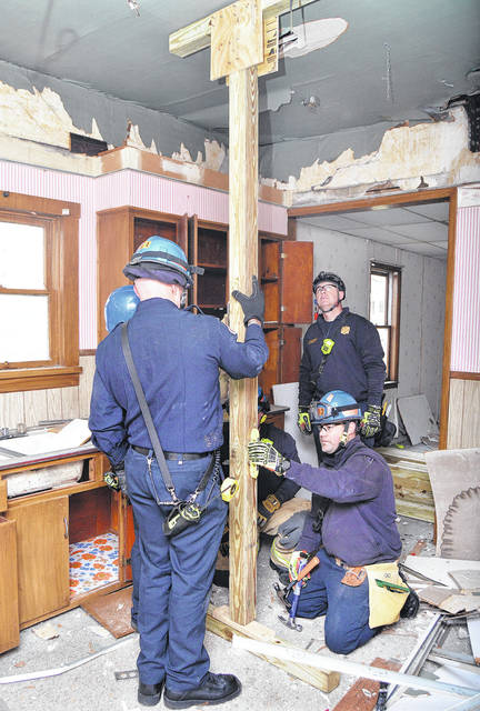 Collapse training for shoring up unstable houses are Sidney Firefighters, left to right, Kyle Barlage, of Russia, Lt. Rod Dyer, of Sidney, Jeff Simon, of Russia, Lt. Jason Truesdale, of Sidney, and Kyle Meyer, of Urbana. The house used by the Sidney Fire Department, Tuesday, Dec. 19, located on North Main Avenue, will eventually be torn down by the Shelby County Land Bank. The firefighters used a field guide made by the U.S. Army Corps of Engineers for guidance.