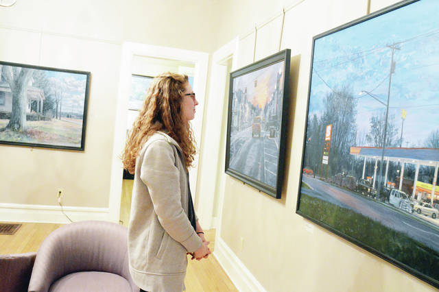 Caity Clark, of Cincinnati, looks over paintings by Phillip Erbaugh, during the opening reception of the painter's Big and Bold art show at the Gateway Arts Council Friday, Dec. 15. The show runs through January 5.