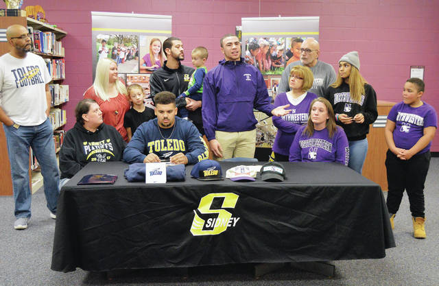 Sidney's Devan Rogers, second from left, front row, listens as his temmate Isaiah Bowser, third from left, front row, taks about the people who have helped him out during a signing ceremony at the Sidney High School library Wednesday. Seated next to the players are their mothers Lisa Rogers, far left, front row, and Melissa Bowser, far right, front row. Standing behind Rogers are, left to right, Roger's dad, Carlose Rogers, sister-in-law Summer Clark, niece Donovia Clark, brother Donovan Clark, and nephew Donovan Clark Jr. Standing behind Bowser are, left to right, his grandma Carol Bowser, grandpa Guy Bowser, sister Mariah Bowser, and brother Jasiah McCluskey.