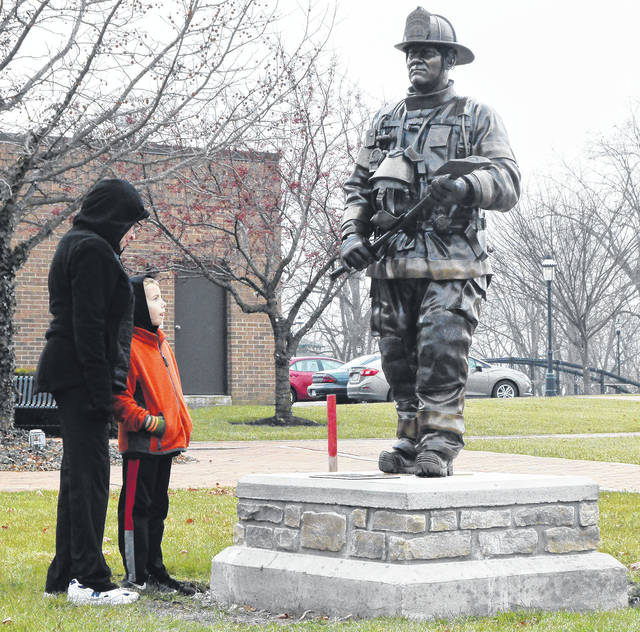 """Dot Schwartz, left, of New Bremen, and her grandson Darren Schwartz, 6, of Minster, son of Scott and Kristy Schwartz, get their first close-up look of a new statue in Lock 1 Park Tuesday, Dec. 19. The statue of a New Bremen firefighter has a plaque that reads """"A tribute to all past, present, and future volunteer firefighters and emergency personnel in recognition of the sacrifices they make in service to their communities."""" The statue was donated by the family of Kenneth Jutte, honoring the sacrifice that he and John Garman made on Oct. 1, 2003. New Bremen firefighters Kenneth Jutte and John Garman died after the roof of a silo blew up while they were fighting a fire at Hoge Lumber and New Knoxville. Schwartz was friends with both firefighters."""