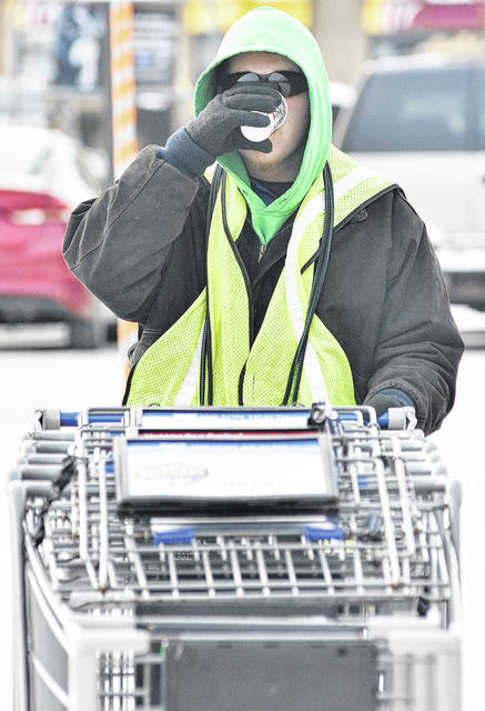 Matthew Mickle, of Sidney, gulps down a Starbucks hot chocolate while bringing in shopping carts at Kroger Thursday, Dec. 28. The temperature was 14 degrees while Mickle was working.