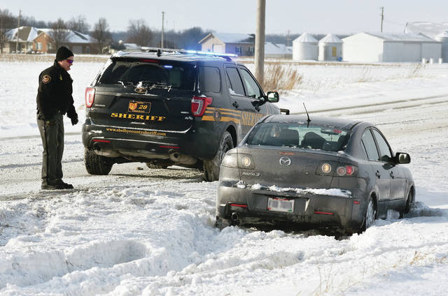 At around 3:30 p.m. Saturday, Dec. 30, a Shelby County Sheriff's deputy talks with the driver of a car that hit a snowy patch on the 11000 block of state route 29 causing them to slide into the ditch and become stuck in the deep snow there. Multiple slide-offs were being reported around the area as drivers go over snow and ice covered patches of road.