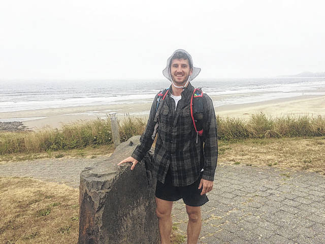 Travis Luck, of New Knoxville, with the Pacific Ocean at his back begins his cross-country trek in Newport, Oregon, in August.