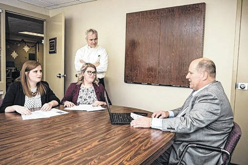 Wright State University student Allison Brown, left to right, James Hamister, associate professor of supply chain management, student Courtney Phibbs and Ben Rhinehart, director of purchasing and trade compliance for Crown, hold a mock negotiation as part of a classroom assignment.