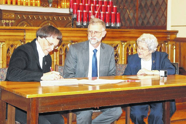 Sister Joyce Lehman, C.PP.S., president of the congregation, signs the deed as Don Rosenbeck, president of the Shrine, and Sister Noreen Jutte look on.
