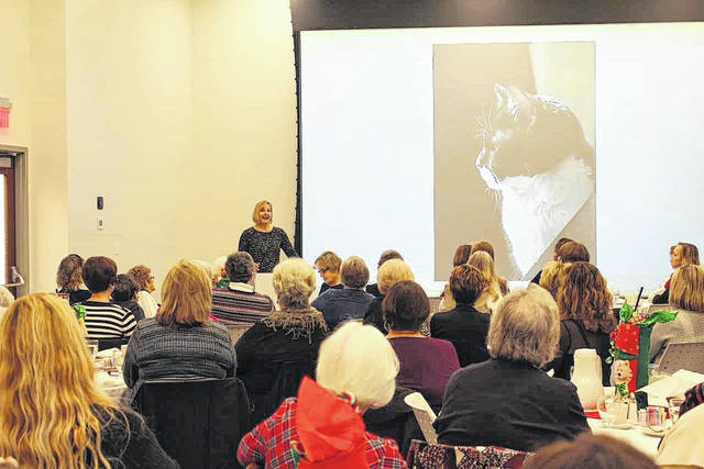 Katrina Kittle shares a photo of her rescue cat, Joey, during her speech at the Christmas luncheon hosted by the Shakespeare Club in the Amos Memorial Library in Sidney, Friday, Dec. 1.