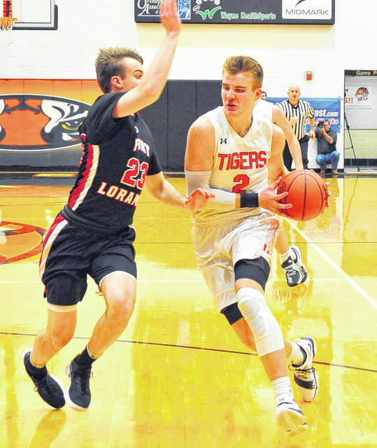 Versailles Justin Ahrens, right, drives to the hoop with pressure from Fort Loramie's Evan Berning during a nonconfernece game on Jan. 9. Both Versailles and Fort Loramie remain ranked in the Associated Press state poll.  Mike Ullery | AIM Media Midwest