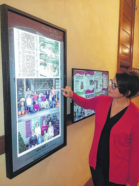 Susie Bergman, marketing director, looks at the digital Legacy Fund Donor Wall at the Maria Stein Shrine of the Holy Relics.