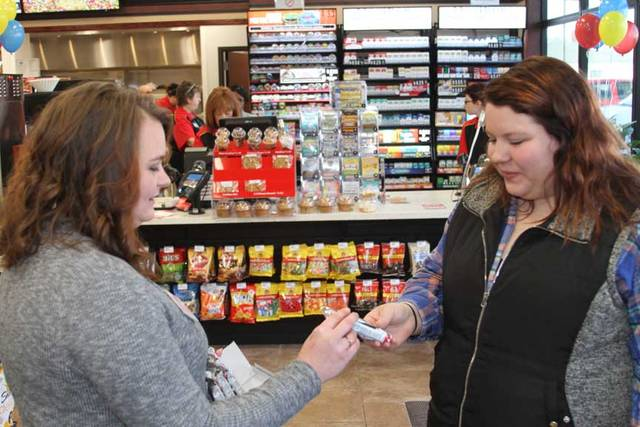 Melinda Fogle, general store manager of Casey's General Store in Jackson Center, shares free samples of a chocolate with Taryn Johnson, of DeGraff, during grand opening celebrations, Friday.