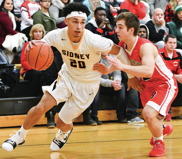 Sidney junior guard Andre Gordon dribbles around Bellefontaine's Donovan Dinovo during a nonconference game on Saturday. Bryant Billing | SIdney Daily News