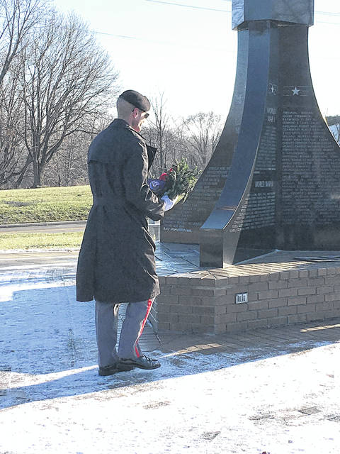 A member of the Veterans Elite Tribute Squad places a wreath at the Veterans Memorial in Forest Hill Cemetery last month.