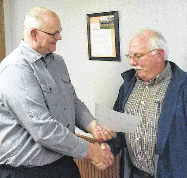 Jackson Center Village Administrator Bruce Metz, left, congratulates firefighter Ron Ludwig on his appointment as deputy chief of the fire department, Monday, Jan. 22.