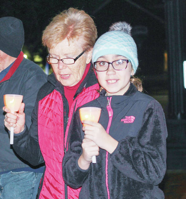 Marge Kitzmiller, of Minster, and Courtney Dulaney, 12, of Anna, daughter of Renee and Nick Dulaney, walk in Monday night's Right to Life vigil held on courtsquare in downtown Sidney.