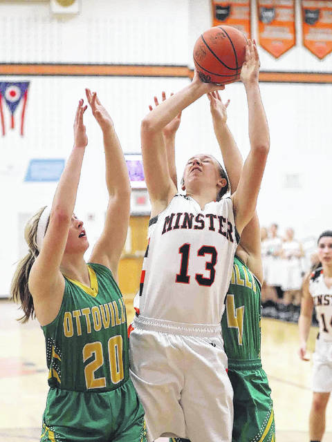 Minster's Paige Thobe puts up a shot against Ottoville's Quinley Schlagbaum, left, and Abi Hilvers during a nonconference game on Saturday's game at Minster.