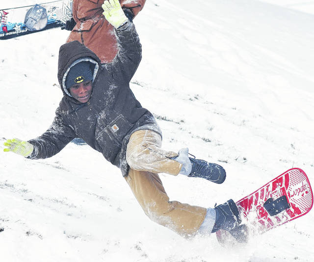 Tyree Williams, 12, of Sidney, son of Mia and Robin Williams, takes a tumble off his snowboard at the Moose golf course recently. The golf course is a popular place for sledding and snowboarding.