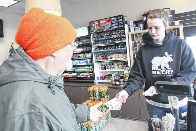 Tony Garza, left, buys a Powerball ticket and Mega Millions ticket from Gabrielle Fields, both of Sidney, at the Karoc Marathon on Wapakoneta Avenue Thursday, Jan. 4. Fields said the gas station has sold a lot of the lottery tickets in the last four days.