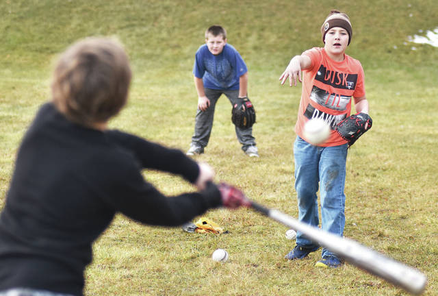 "Taking turns hitting baseballs at McMillen Park Wednesday, Jan. 10, are, left to right, Dallas Carr, 9, and his brother Justin Fent, 10, both the children of Kasey Carr, and Cody Powers, 13, all of Sidney, son of Bill Hughes and Linda Powers. Cody said of three boys ""We play sports a lot. We're athletic."" The three boys said they play together almost every day regardless of the weather."