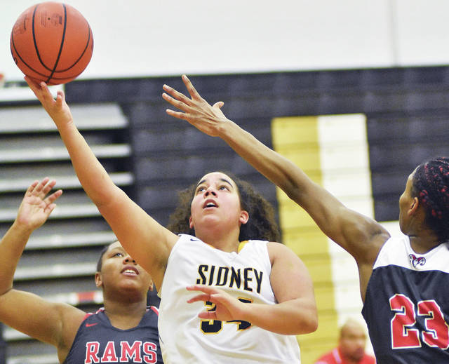 Sidney's Kyana Johnson shoots while covered by Trotwood's Milliani King, left, and Shaiquel McGruder on Wednesday at Sidney.