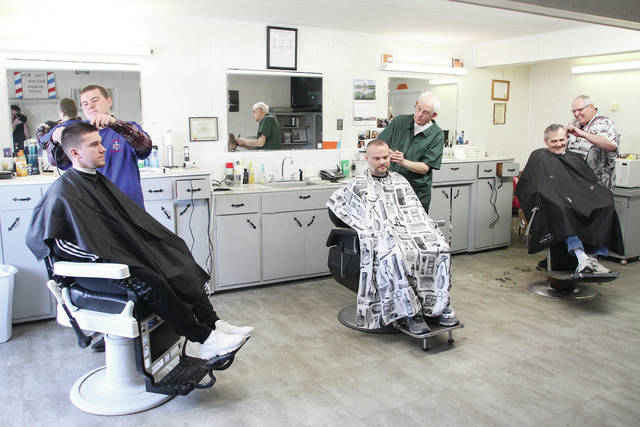 Cutting hair, Thursday, Jan. 25, left to right, are Jordan Perkins, Ron Miller and Ron Geise, all of Sidney. Getting their haircuts are, left to right, Brady Gaylor, Alex Perkins, and Carey Albaugh, all of Sidney. Jordan Perkins recently purchased the 4th Avenue Barber Shop from Geise, who purchased it from Miller in 1999.
