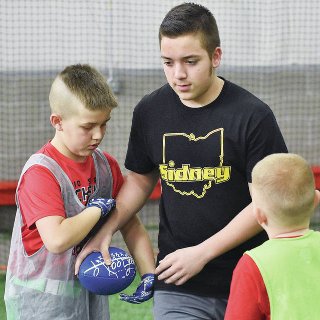 """Braxton Davis, far left, is handed the ball by Sidney freshman Conor Linniman during a winter football camp run by Devin Brautigam at APEX Sports Zone. Watching the handoff is Landon Smith. The camp is a primer for Coach Brautigam's Football Program for kids in kindergarten through 4th grade. The kids football program runs from March through April 22. Brautigam says his programs goal is """"to be involved with the youth in our community. We are going to put Sidney on the map for youth football."""""""