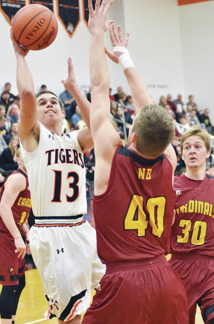 Jackson Center's Bryce Sosby shoots over New Bremen's Luke Vonderhaar as New Bremen's Andrew Bowers, right, watches at Jackson Center on Saturday.