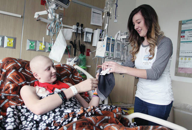 Jackson Hogenkamp, left, 15, of Minster, son of Scott and Shelly Hogenkamp, takes a Minster Wildcats hat from Abbey Goubeaux. Hogenkamp was one of many kids who received toys from Goubeaux at Dayton Children's Hospital, Monday, Jan. 30. Hogenkamp is being treated for osteosarcoma, a form of bone cancer.