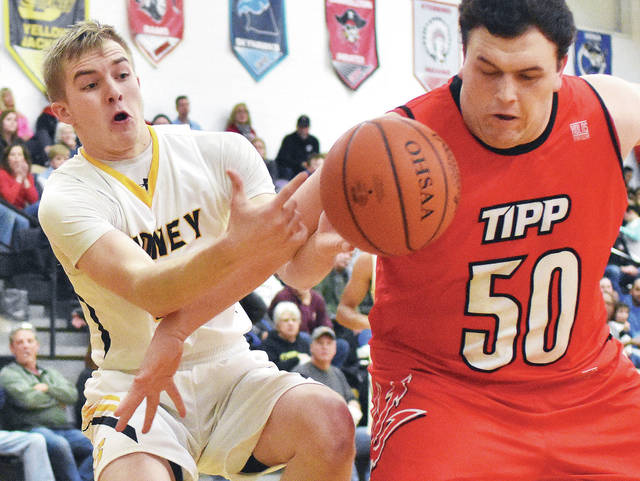 Sidney's Ryan Heins, center, reaches for a loose ball while blocked by Tipp's Noah Bledsoe, right, at Sidney on Tuesday.