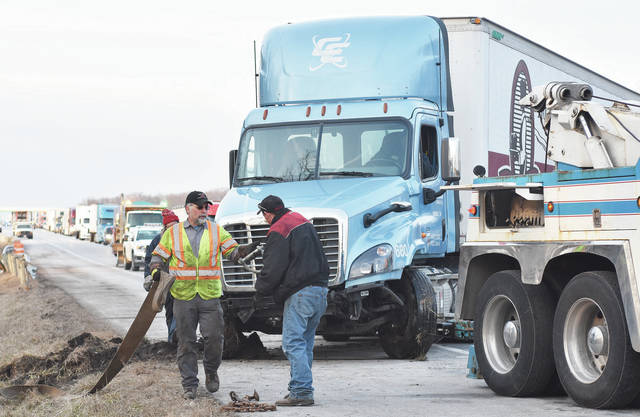 A semi tractor trailer is towed out of the ditch where it crashed in the south bound lane of I-75 just south of exit 102. Traffic was backed up for miles until the truck was finally freed at around 5:30 p.m. Wednesday, Jan. 31.