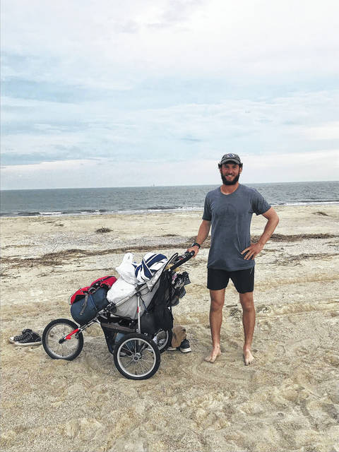 """Travis Luck, of New Knoxville, poses for photo with the Atlantic Ocean in the background in Tybee Island, Georgia, Dec. 20. He had just completed a coast-to-coast walk that began with the Pacific Ocean in the background at Newport, Oregon, in August. Luck walked the more than 3,000 miles in 133 days. """"The exact mileage, I can't be sure. I know it's over 3,000 miles; however, I stopped tracking exact number about halfway through my trip,"""" Luck said."""