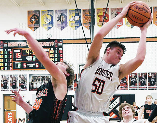Jarod Schulze of Minster, right, wins a rebound battle against Versailles' Evan Hiestand during a Midwest Athletic Conference game on Friday in Minster.