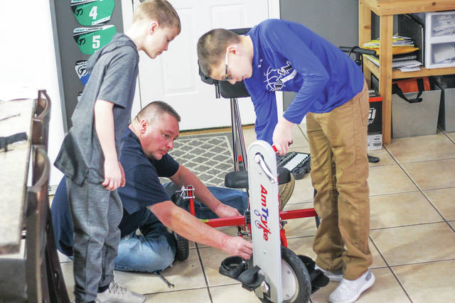 Eric Jones from A&E Racing works with his sons, Ethan, 12, right, and Eli, 8, to put together an AmTryke together for a local resident. The AmTryke project is sponsored locally by the Sidney Kiwanis Club.