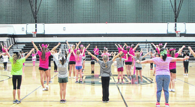 Girls in Greenville learn cheerleading basics from Greenville High School cheerleaders during Cheer Fun Day, Saturday, at the high school. They will perform during half time of the junior varsity basketball game tonight.