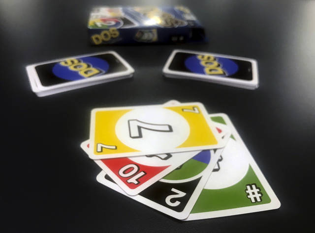 Mattel's new card game Dos is displayed on Monday, Feb. 12, 2018, in New York. Mattel is launching the new card game next month in hopes of giving its nearly 50-year-old Uno brand a second life. Dos has similar rules as Uno, except players make two piles of cards and can throw down two cards at a time instead of one. (AP Photo/Jenny Kane)