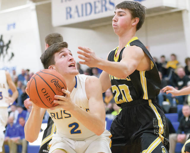 Russia junior forward Jordan York shoots with pressure from Botkins' Spencer Heuker during a Shelby County Athletic League game on Friday at Claire C. Naveau Gymnasium in Russia.
