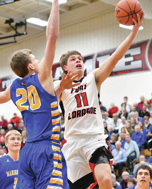 Fort Loramie sophomore guard Nick Brandewie shoots with pressure from Marion Local's Nick Tangeman during a nonconference game on Saturday.
