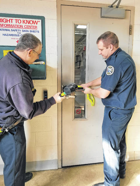 Lt. Tony McLain demonstrates with Firefighter Brian Lundy how the new Forcible Entry Tool works to forcibly open a closed/locked door. The tool is light weight and made to be used by one person which is extremely helpful when there are multiple calls.