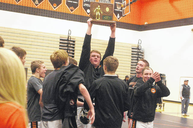 Versailles senior Jeffrey Ware holds up a trophy after the Tigers won the OHSAA Regional State Duals championship last week.