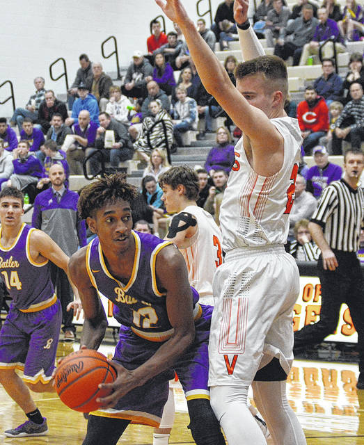 Butler's Bryant Johnson shoots with pressure from Versailles' Justin Ahrens during a game on Tuesday in Versailles.