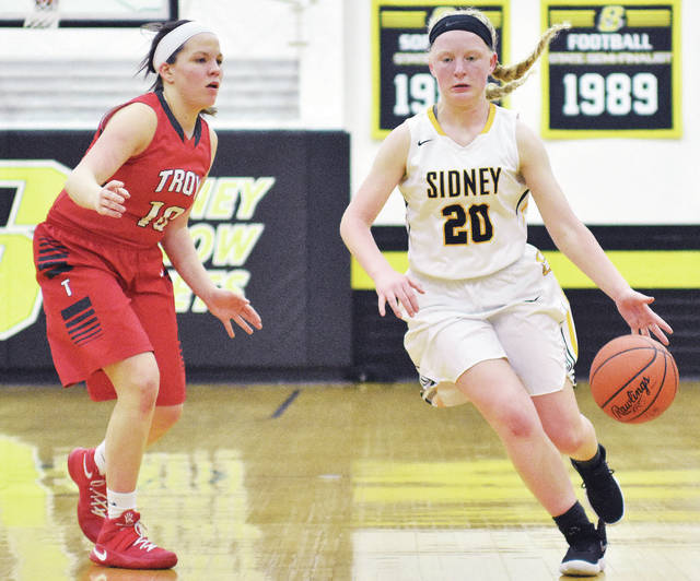 Sidney's Carly Dean heads down the court followed by Troy's Makenna Taylor during a Greater Western Ohio Conference game at Sidney on Wednesday. The Trojans scored the last four points to earn a 36-33 win.
