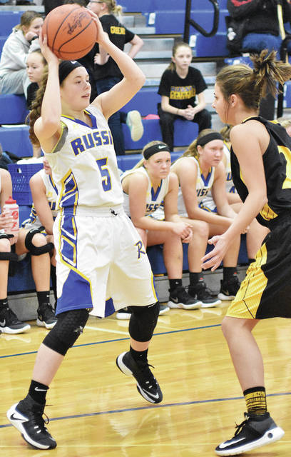 Russia's Kendall Monnin looks to pass with pressure from Botkins' Kinley Topp during the fourth quarter of a Shelby County Athletic League game at Russia on Thursday.