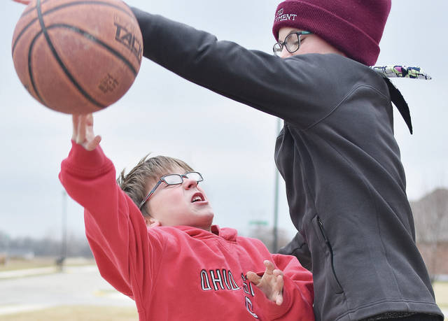 Cooper Meyer, left, 7, was finding it difficult to get the basketball past the defense of his sister, Carissa Meyer, 11, during a game of b-ball at a friend's house in Fort Loramie, Thursday, Feb. 1. They are the children of Dana and Bryan Meyer, of Fort Loramie.