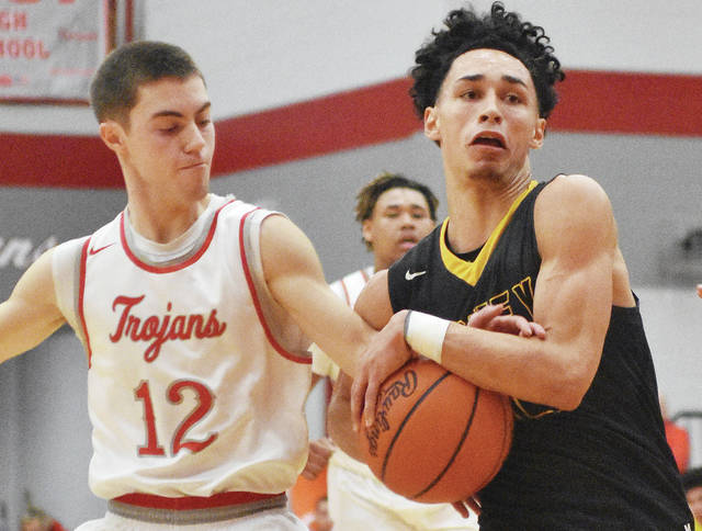Sidney junior guard Andre Gordon dribbles with pressure from Troy's Cole Brogan during a Greater Western Ohio Conference game on Friday at the Trojan Activities Center. Sidney scored the first 13 points of the third quarter to run away to a 58-35 win.