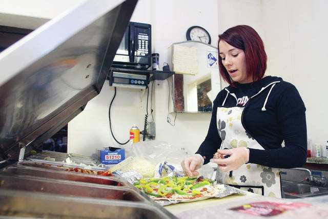 Grace Fear, of Newport, puts toppings on a pizza at Keyhole Pizza, in Newport, Saturday, Feb. 3.