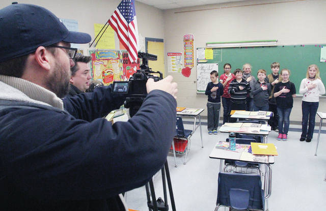 """Fox 45 and ABC 22 creative services producers Ted Dryden, left to right, of Springfield, and Todd Carter, of Tipp City, prepare to film the students of Debra Naumann's fourth-grade Christian Academy class reciting the Pledge of Allegiance. The taping held Tuesday, Feb. 6 was for the Fox 45 """"Morning Pledge"""" which is played Monday through Friday. The creative services producers filmed several other classes reciting the pledge. They did not know when the video would air."""