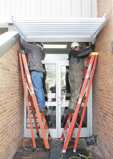 Westerheide Construction employees Nate Bollheimer, left, and Mark Buehler, both of McCartyville, put up a sunshade canopy, Tuesday, Feb. 6, that is part of a west entry renovation project at the Sidney-Shelby County YMCA. The project started in early Dec. of last year, and includes replacement of doors, new flooring, new lights call bollards that will illuminate the sidewalk, a privacy fence, new shrubs and the sidewalk will be repaved after it warms up. The project was paid for with donations. The renovation was done at the same time as a leak in the wall of a basement stairwell next to the western doors was fixed. The leak was fixed with YMCA funds.