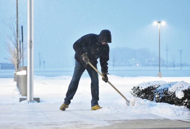 A light snow falls around Fort Loramie High School maintenance employee Dennis McGowan, of Minster, as he shovels the main walkway at the entrance to his school at 7:30 a.m. Wednesday, Feb. 7. Fort Loramie High School initially pushed back opening to 9:30 a.m. and later canceled school because of the snow and road conditions.