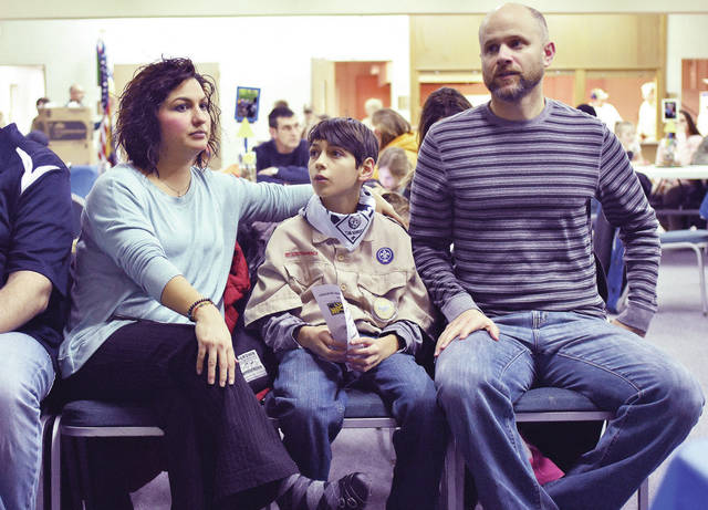 Xander Keller, center, 11, flanked by his parents Cristina, left, and Rob Jenkins, all of Sidney, waits to be elevated from the rank of Cub Scout to Boy Scout. Xander took part in the Arrow of Light crossover ceremony 2018 at St. Pauls Church Thursday, Feb. 8. Also becoming Boy Scouts in the ceremony were Josef Bernardi, Ben Brunswick, Logan Rose and Landon Sibert.