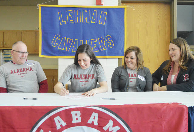 Lehman Catholic's Kelsey Weber, second from left, signs a letter of intent to play at Alabama on Friday. Watching are, left to right, her parents Paul and Tonya Weber and Greater Dayton Rowing Association Coach Abby Beach.