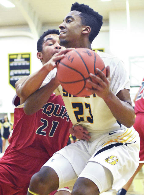 Sidney's Josiah Hudgins drives with pressure Piqua's Qurri Tucker during a Greater Western Ohio Conference game at Sidney on Friday.